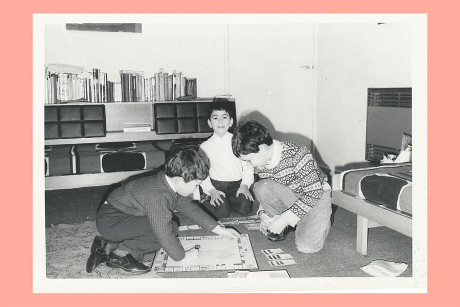 Printed black and white of Barrie and Marion Liss's children playing a board game on the floor, around 1970