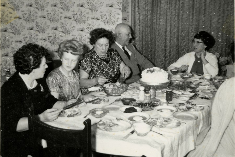 Christine and several members of her family seated around a dining table in Leyton, London. c. 1968. Object number 96/2008